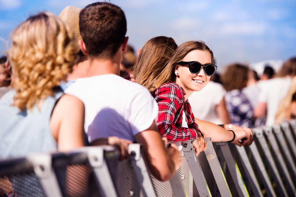 Teenage girl with her friends at summer music festival standing under the stage at the crowd control barrier