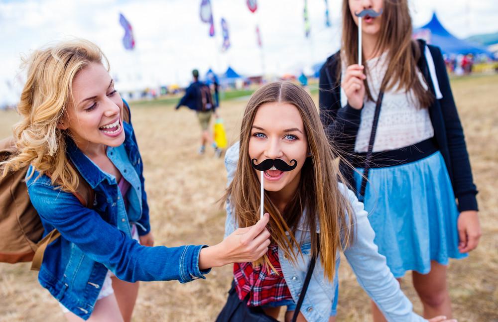 Teenage girls at summer music festival having fun with fake mustache