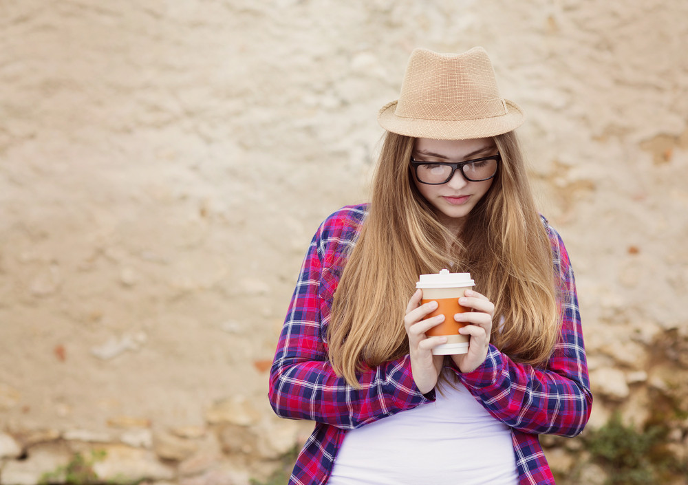 Teenage hipster girl enjoying her take away coffee in city street