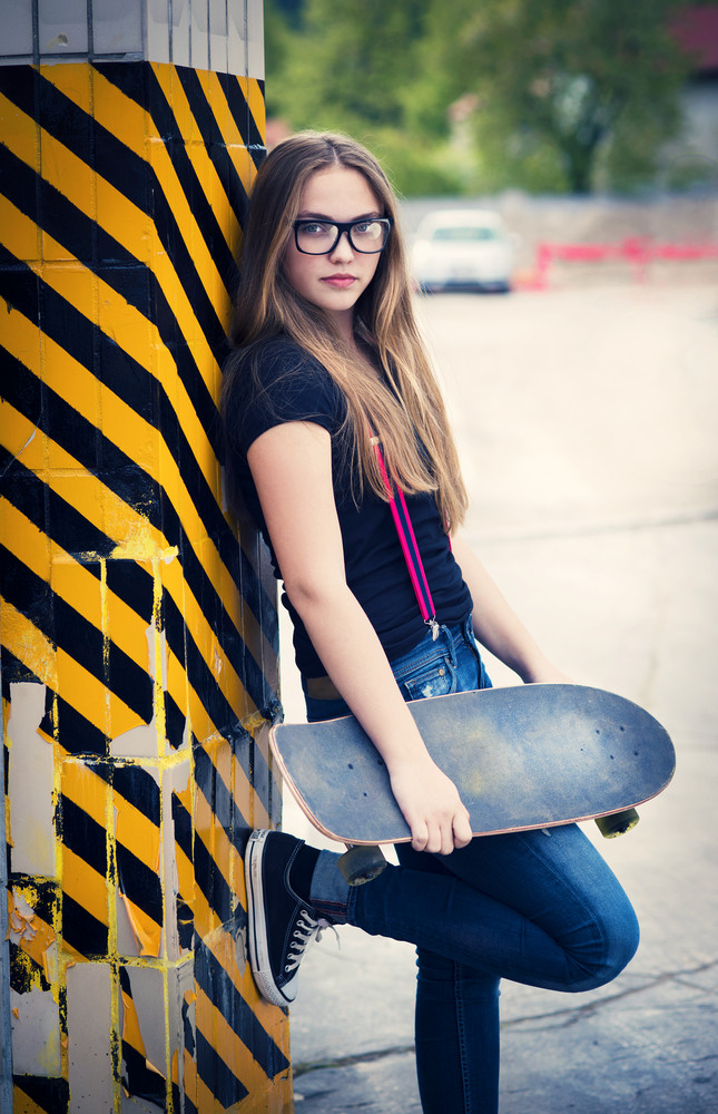 Teenage hipster girl with longboard is standing by the black and yellow striped warning wall