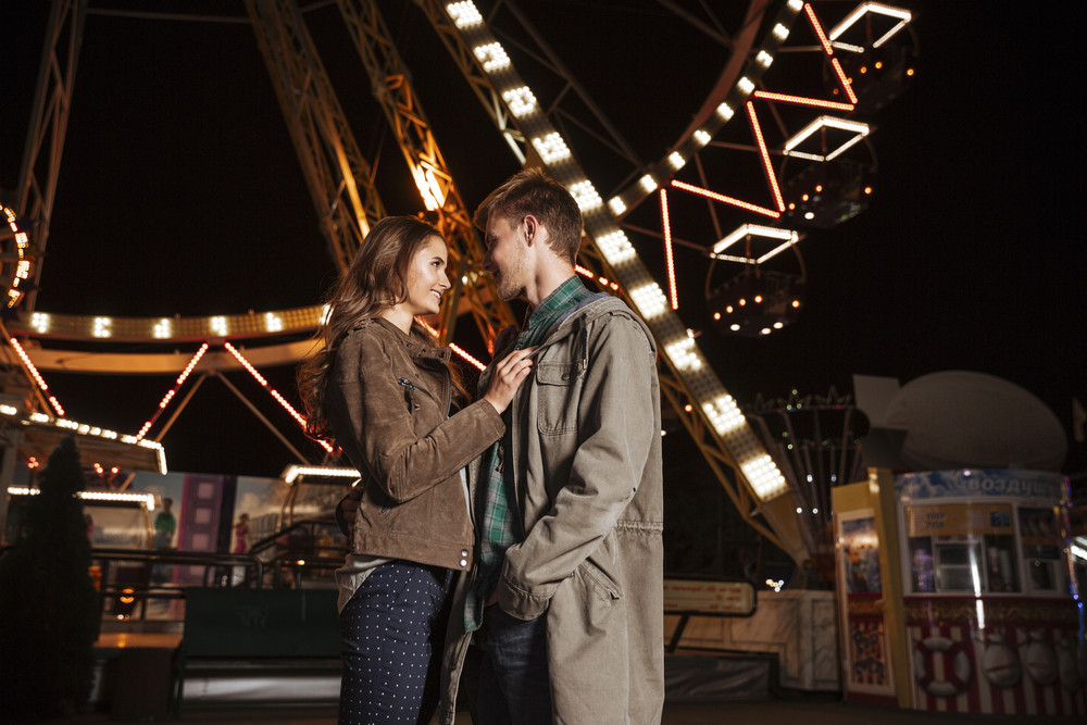 Teenager couple in amusement park. in warm clothes