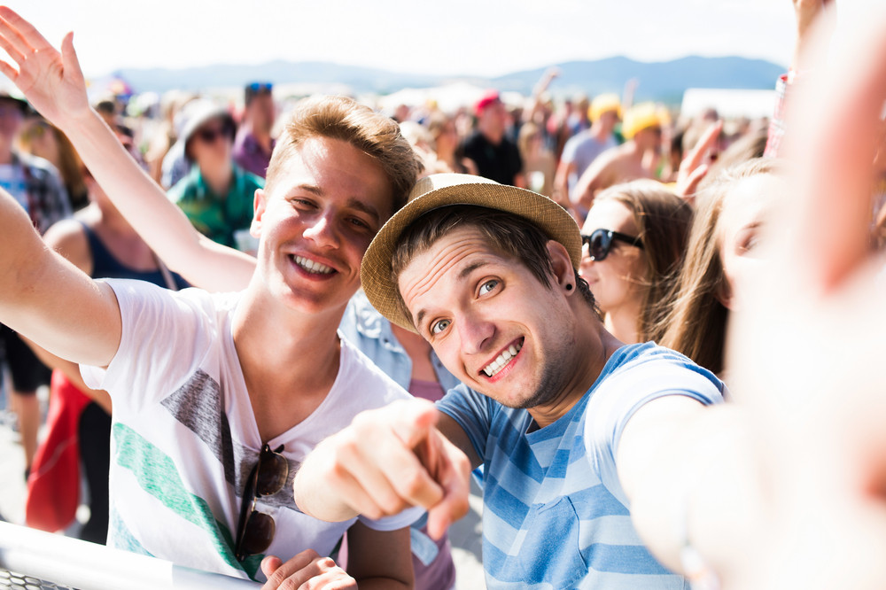 Teenagers at summer music festival in crowd taking selfie, enjoying themselves