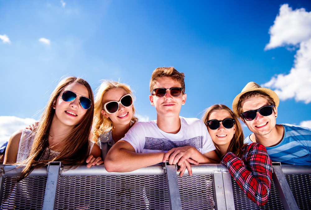 Teenagers at summer music festival standing under the stage at the crowd control barrier