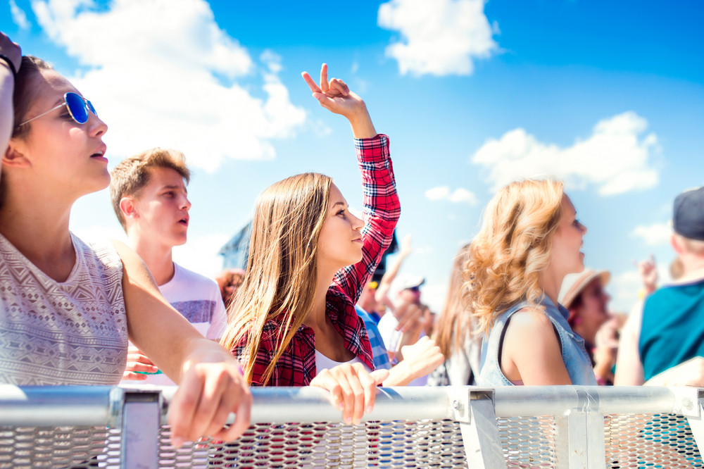 Teenagers at summer music festival under the stage in a crowd enjoying themselves, dancing and singing