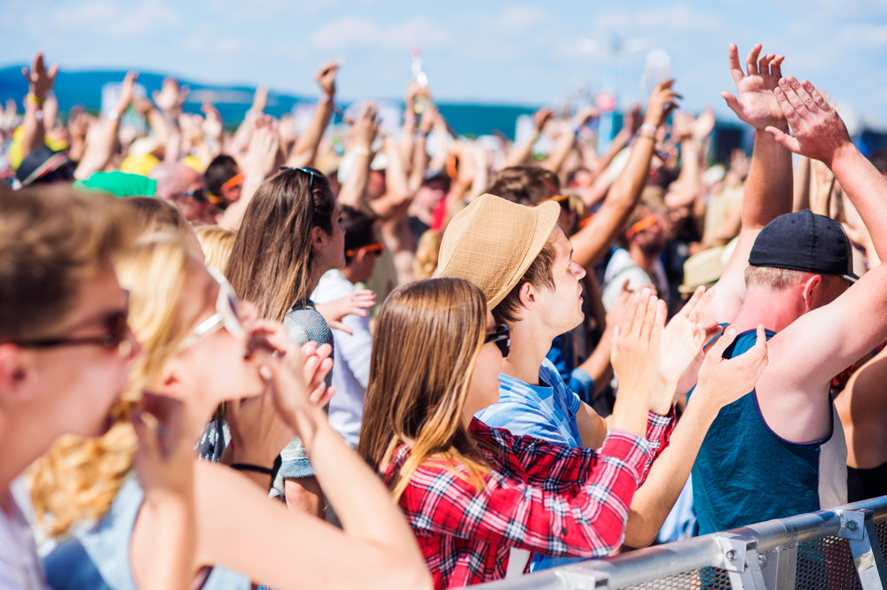 Teenagers at summer music festival under the stage in a crowd enjoying themselves, whistling, clapping, singing