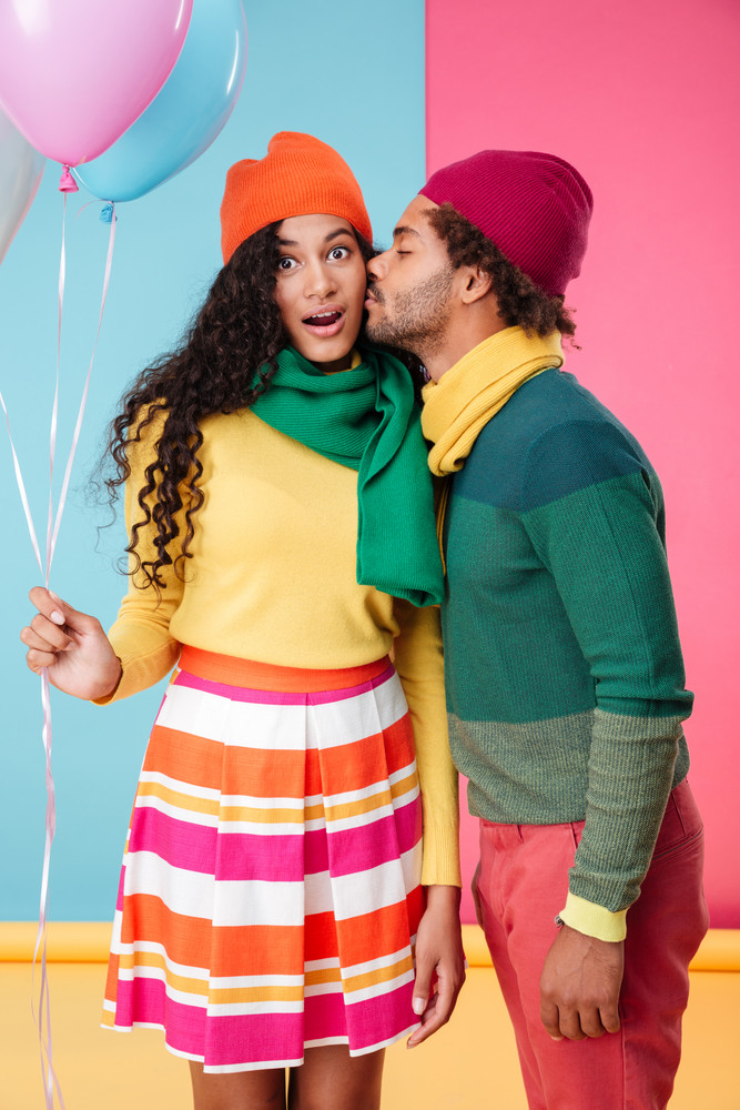 Tender african young man in hat and scarf standing and kissing his girlfriend with balloons
