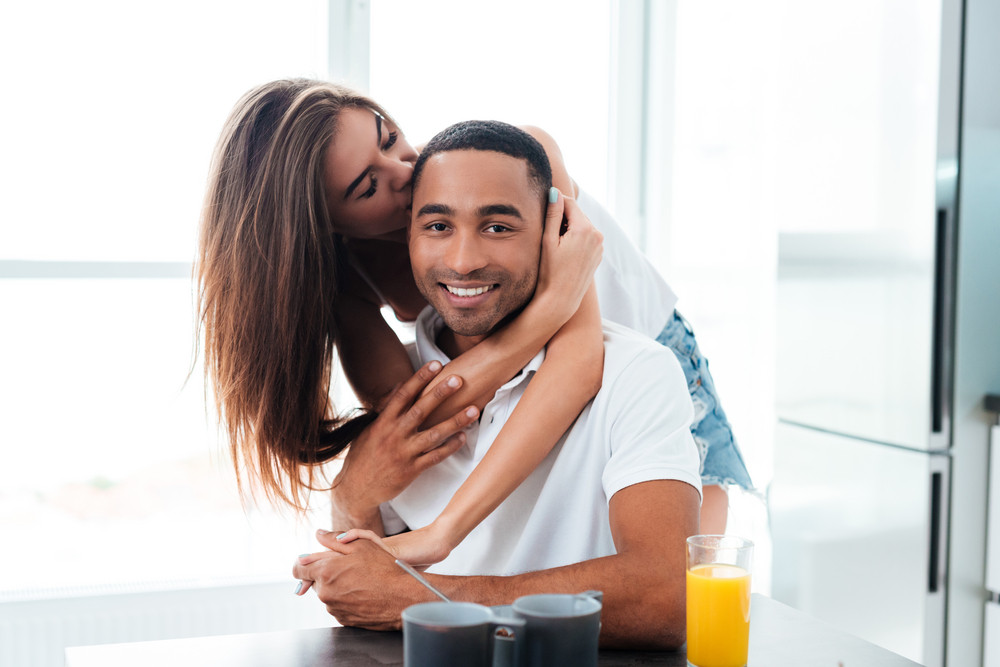 Tender young couple hugging and having breakfast on the kitchen