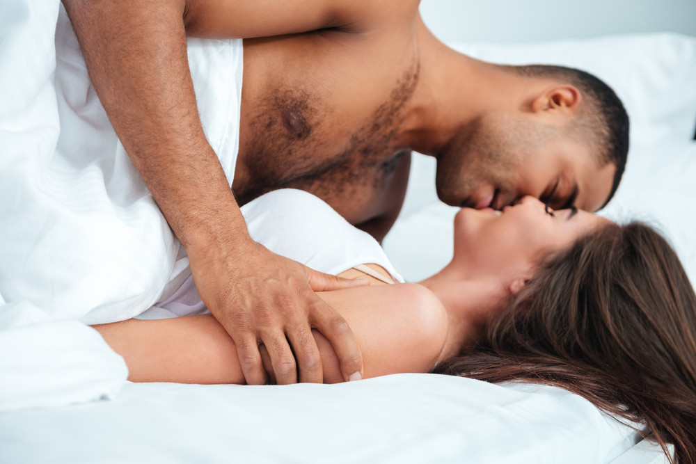 Tender young couple kissing in bed at home
