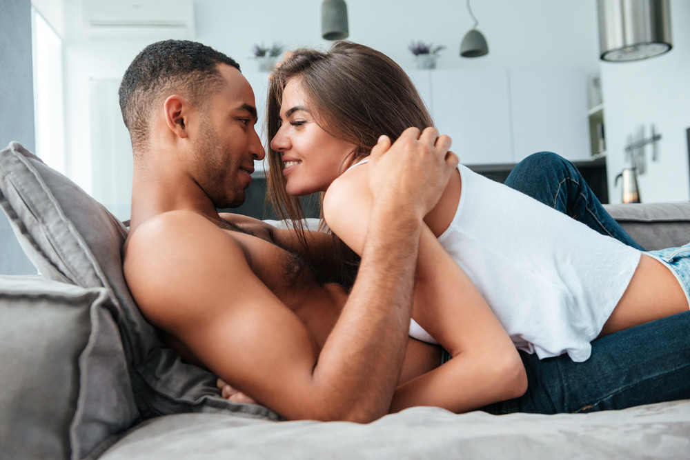 Tender young couple lying and hugging on couch at home