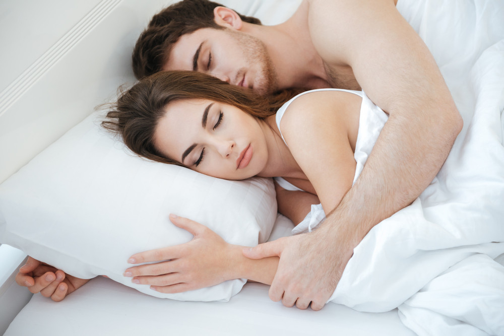 Tender young couple lying and sleeping together in bed