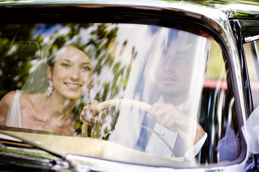 The bride and groom have fun behind the wheel of retro car