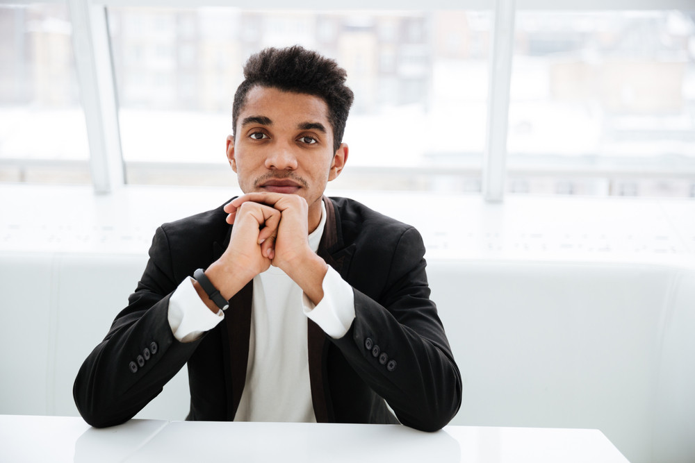 Thoughtful african business man in black suit sitting at the table with hands near the face in office and looking at camera