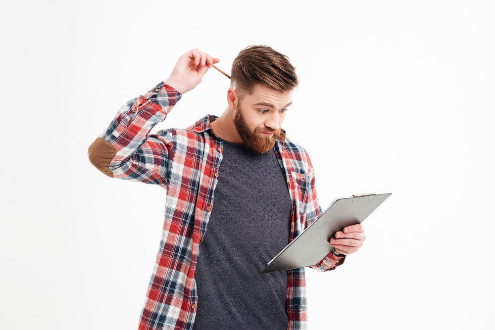 Thoughtful annoyed bearded young man in plaid shirt scratching his head by hand over white background
