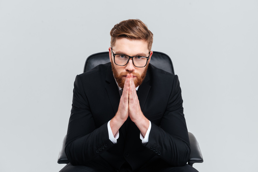 Thoughtful bearded business man in glasses and black suit sitting on armchair and holding his hands near the face as well as looking at camera. Isolated gray background