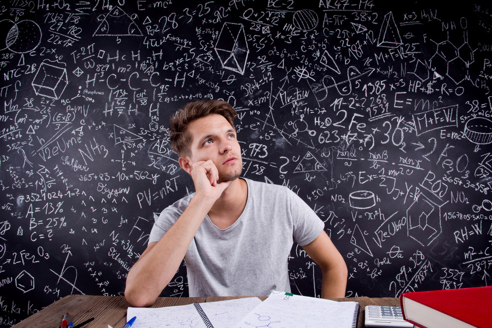 Thoughtful hipster student doing his homework in front of a big blackboard