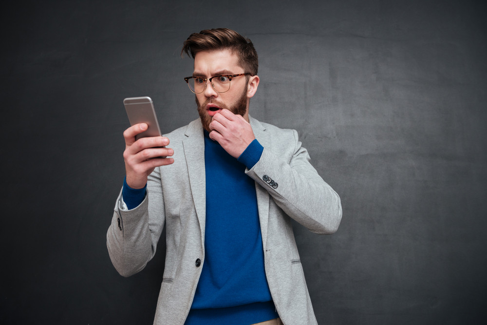 Thoughtful hipster with phone. man in glasses. isolated black background