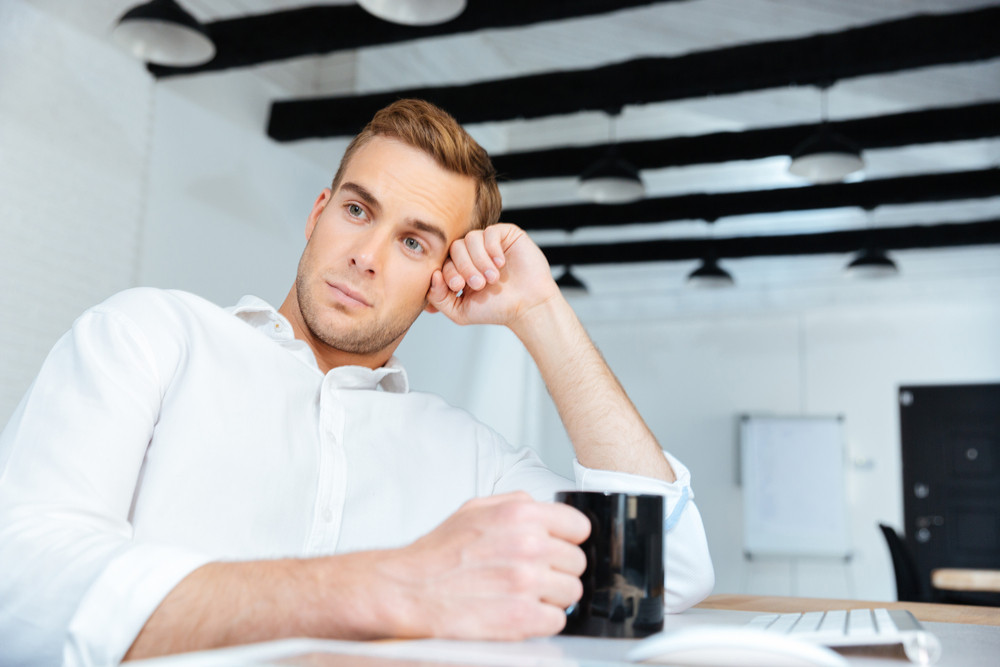 Thoughtful peaceful young businessman drinking coffee and thinking at workplace