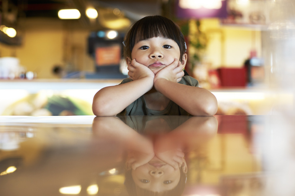 Thoughtful portrait of little girl lay on the table