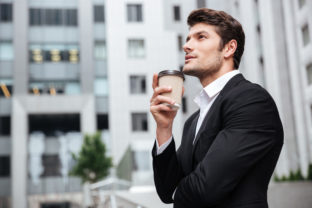 Thoughtful young businessman drinking take away coffee and thinking near business center
