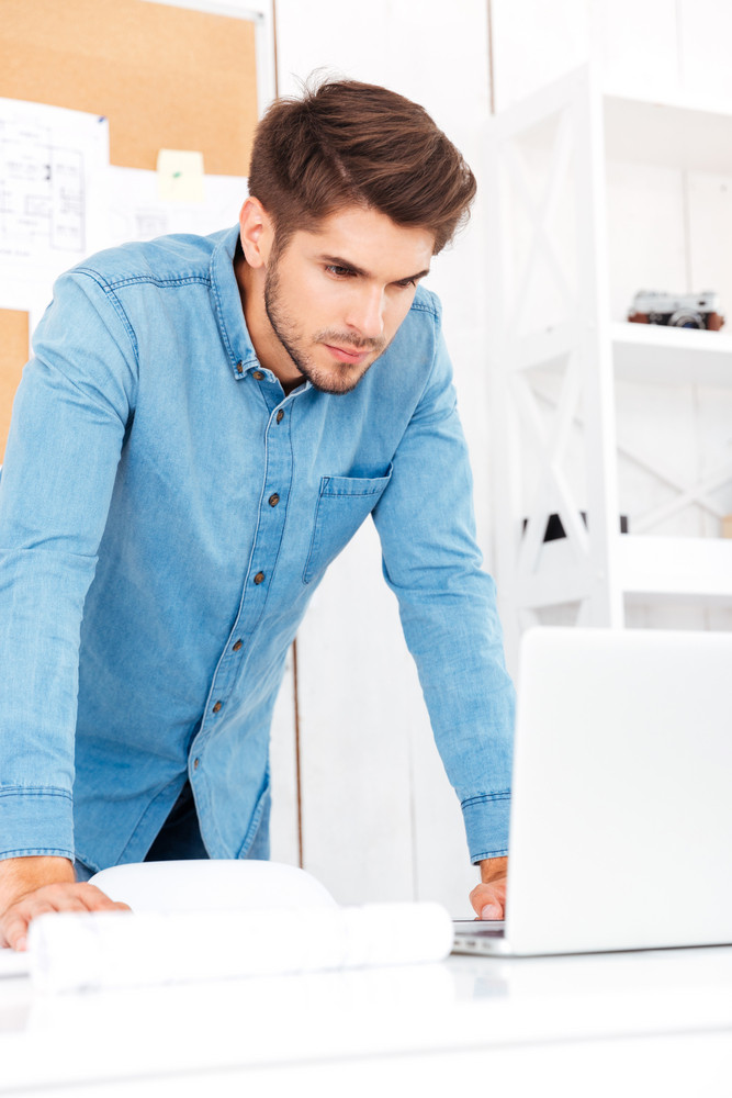 Thoughtful young businessman looking at laptop while standing in office
