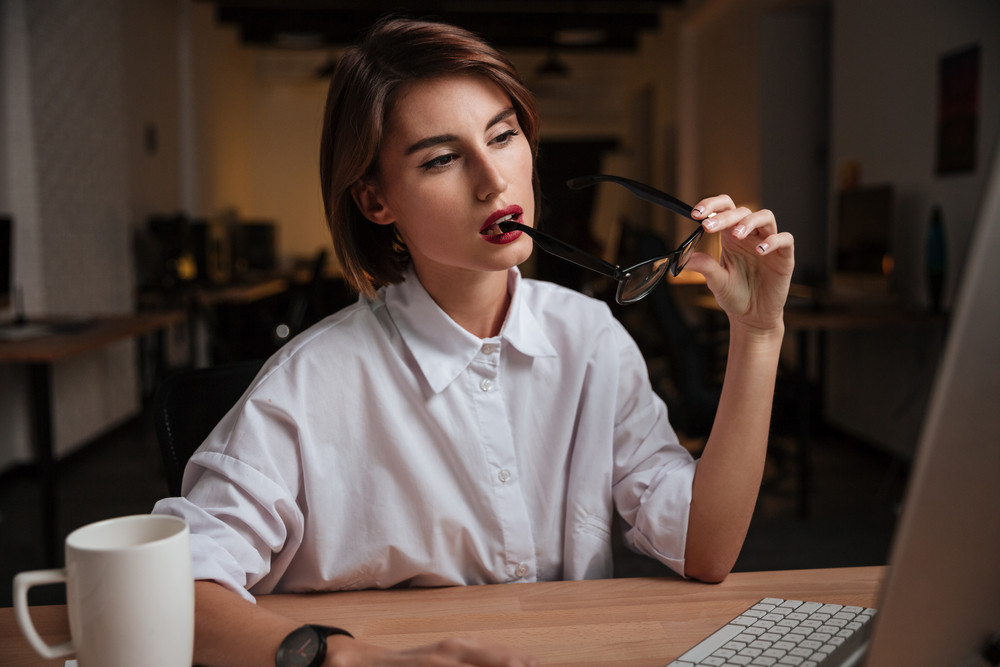 Thoughtful young businesswoman holding glasses and thinking in office