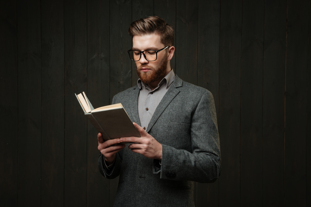 Thoughtful young man in eyeglasses standing and reading book isolated on the black wooden background