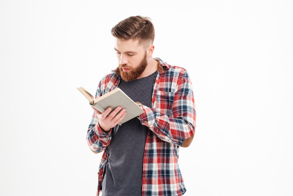 Thoughtful young man standing and reading book over white background