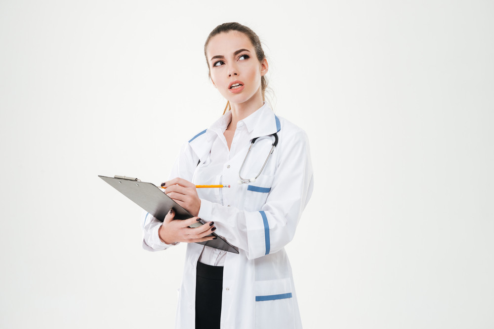Thoughtful young woman doctor thinking and writing on clipboard over white background