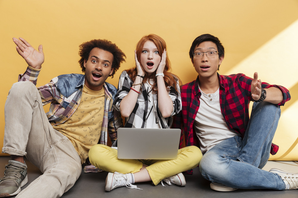 Three amazed astonished young people sitting and using laptop over yellow background