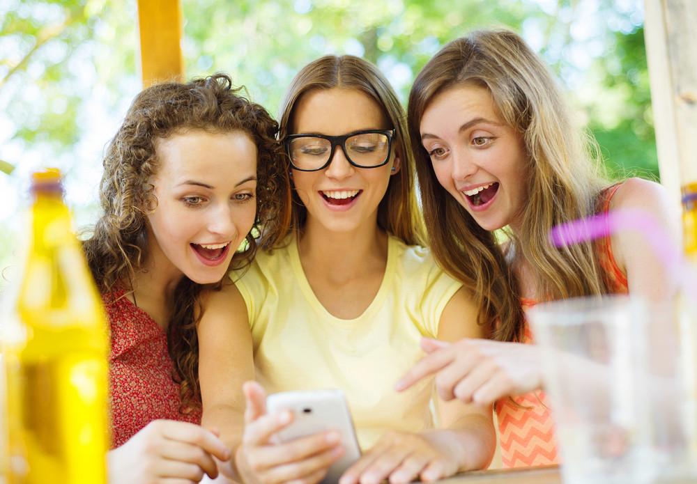 Three beautiful girls drinking and having fun with smartphone in pub garden