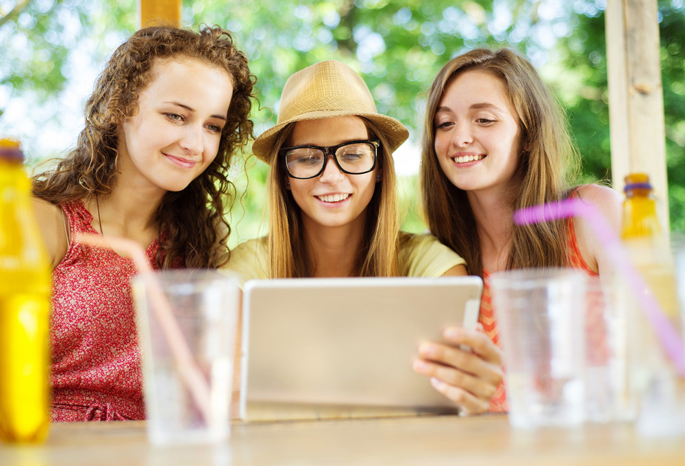Three beautiful girls drinking and having fun with tablet in pub garden