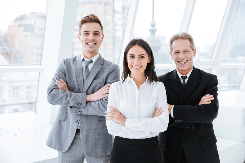 Three business people with arms crossed standing near the window in conference room