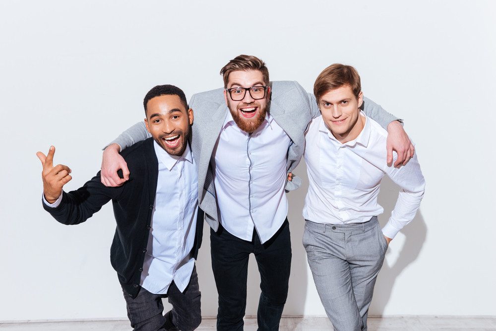 Three cheerful young men standing and smiling together over white background