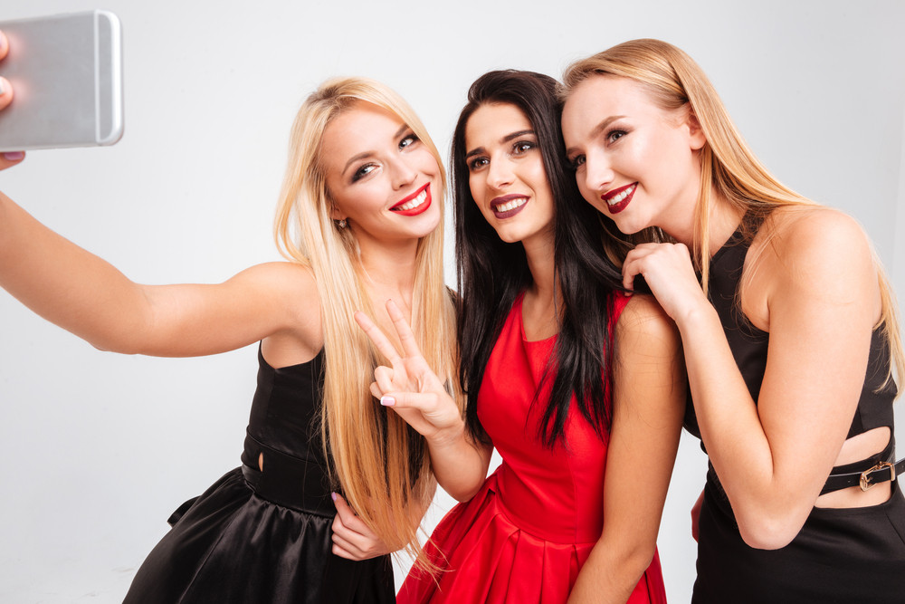 Three cheerful young women making selfie with cell phone over white background