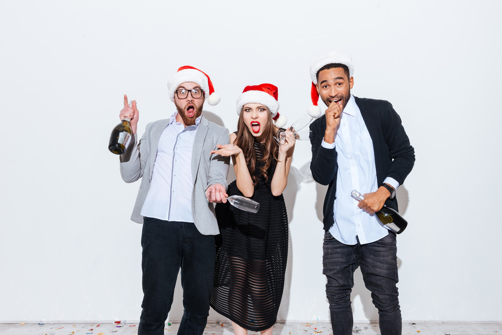 Three funny amazed young people holding bottle and glasses of champagne over white background