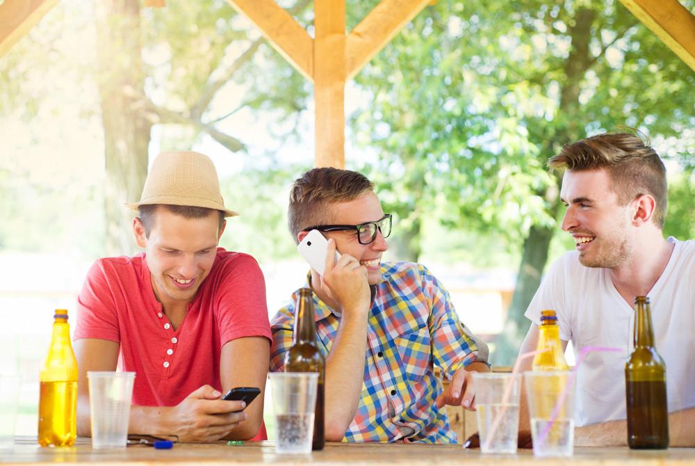 Three happy friends drinking and having fun in pub garden