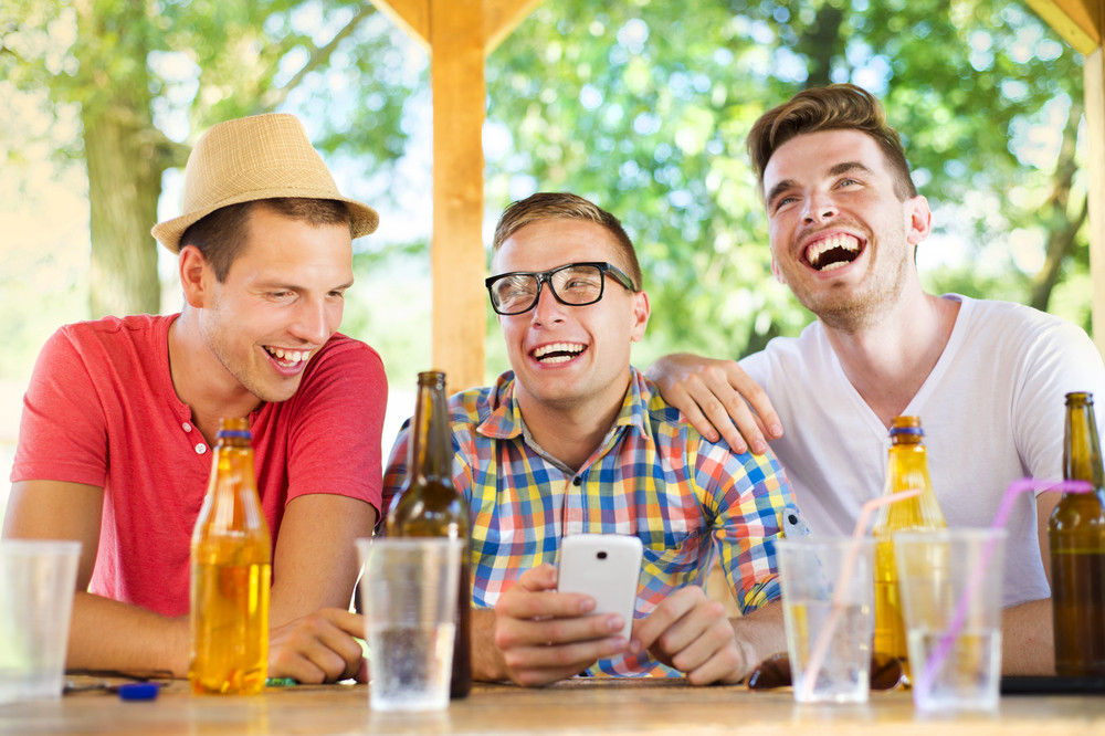 Three happy friends drinking and having fun with smartphone in pub garden