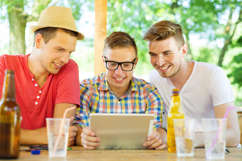 Three happy friends drinking and having fun with tablet in pub garden