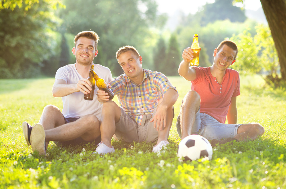 Three happy friends spending free time together in park sitting on grass, drinking beer and chatting