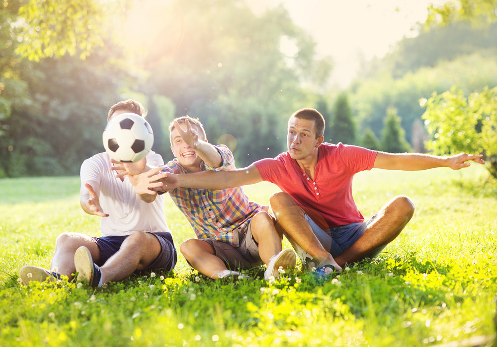 Three happy friends spending free time together in park sitting on grass, playing with soccer ball