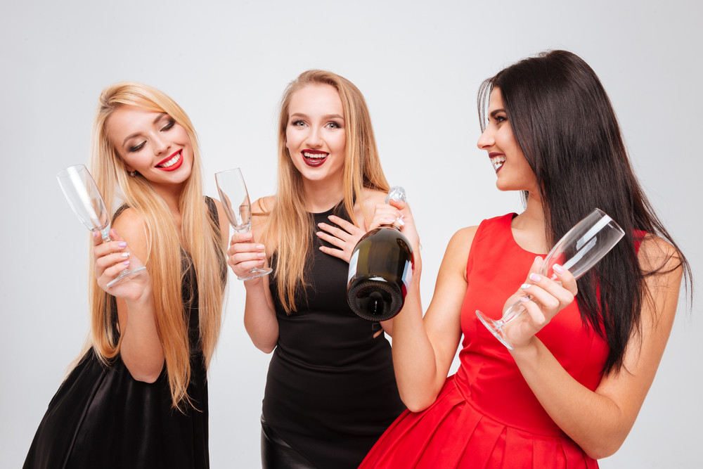 Three happy pretty young women drinking champagne together over white background
