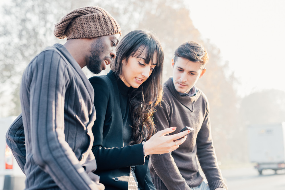 Three multiethnic woman and men friends outdoor in city back light, chatting and holding smart phone - friendship, social network, conversation concept