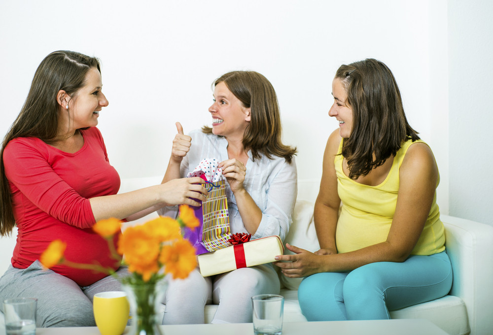 Three pregnant women sitting on sofa and looking at baby shower gifts
