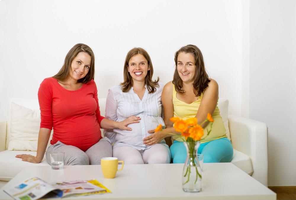 Three pregnant women sitting on sofa and posing