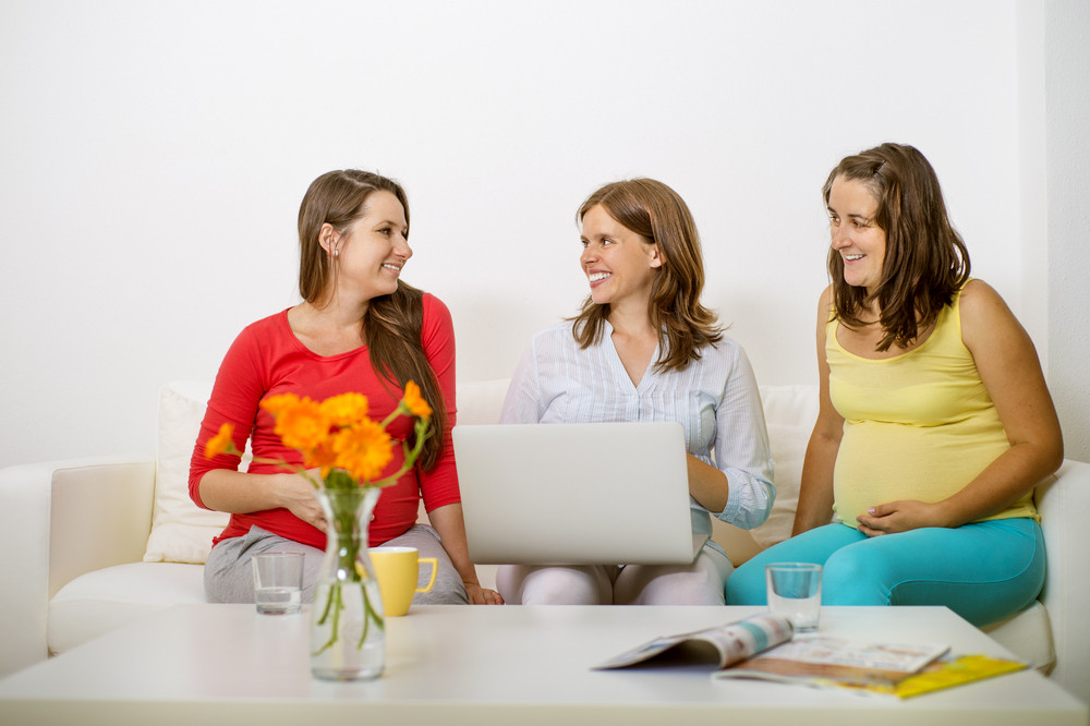 Three pregnant women sitting on sofa, chatting and using laptop