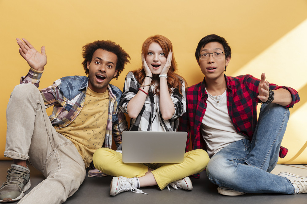 Three surprised young people sitting and using laptop over yellow background