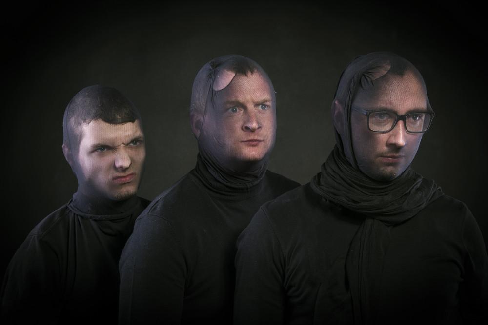 Three thiefs in balaclavas on their faces, dressed in black. Studio shot on black background.