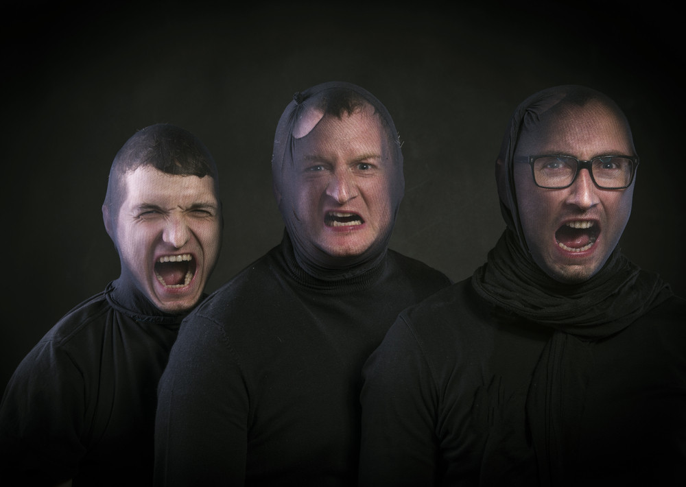 Three thiefs in balaclavas on their faces, dressed in black. Studio shot on black background.