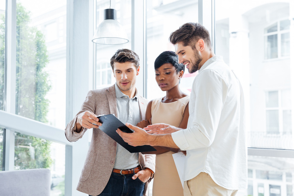 Three young business people standing and discussing business plan together in office