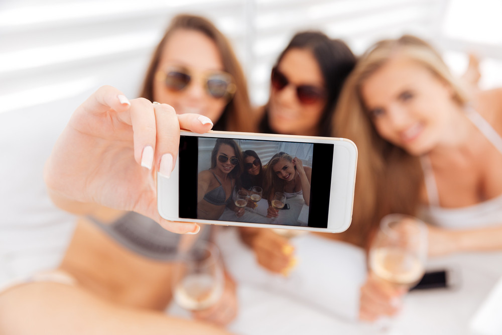 Three young smiling happy girls making selfie holding glasses with drinks
